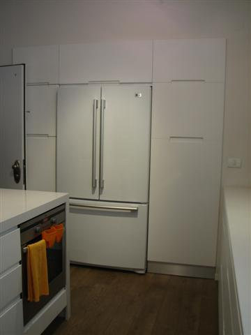 white fridge in kitchen. white fridge surrounded by even more cabinets and there\u0027s a kitchen island as well. in